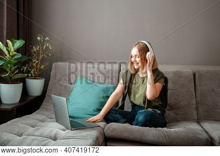 Happy Young Woman Is Sitting On Sofa With Laptop In Headphones. Remote Work, Online Study Or Online