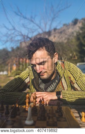 Man Plays Chess Outdoors On A Sunny Day. Portrait Of A Young Man During A Game Of Chess.