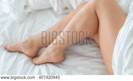 Slim, Perfect And Beautiful Crossed Woman Legs On Bed. Cropped Image Of Erotically Lying On Bed Beau