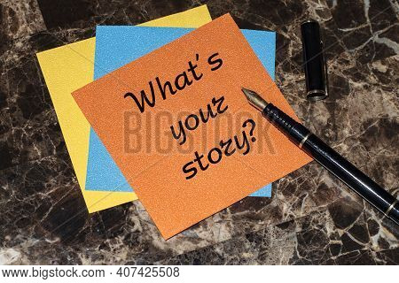 What's Your Story, A Question Mark, A Note On An Orange Sticker Lying On A Marble Table Along With A