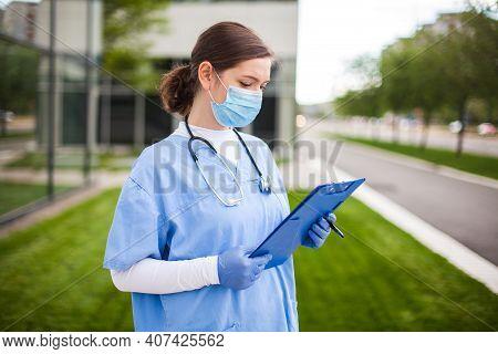 Female Uk Nhs Doctor Holding Blue Clipboard Standing Outside Hospital Clinic Street Entrance,frontli