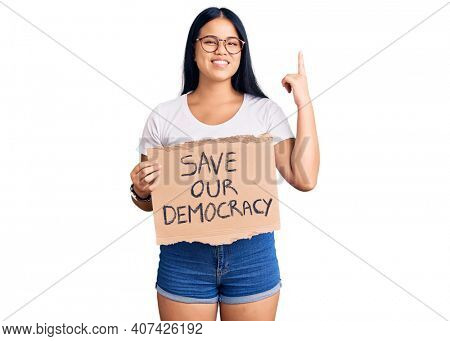 Young beautiful asian girl holding save our democracy protest banner surprised with an idea or question pointing finger with happy face, number one