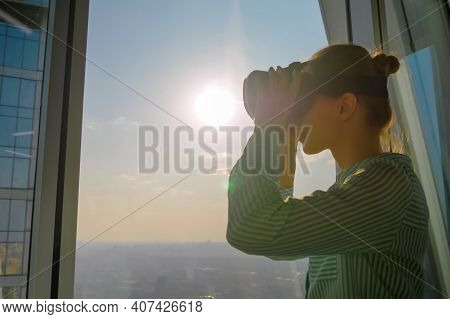 Woman Using Virtual Reality Headset And Looking Around Against View On Cityscape From Panoramic Skys