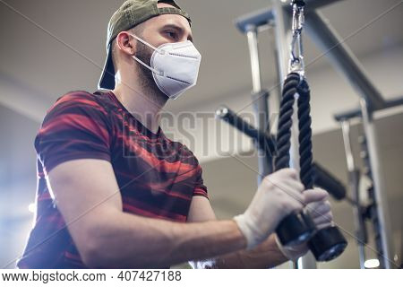 Young Caucasian Man Working Out On Lat Pull-down Machine In Re-open Us Gym,wearing Protective Latex
