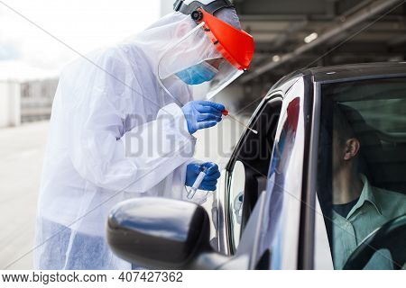 Medical Worker In Ppe Performing Nasal & Throat Swab On Person In Vehicle Through Car Window,covid-1