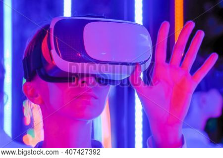 Woman Using Virtual Reality Headset And Moving Hand At Interactive Technology Exhibition With Colorf
