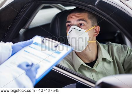 Male Driver Wearing Protective N95 Face Mask Sitting By Left Drive Wheel In Uk Drive-thru Covid-19 T