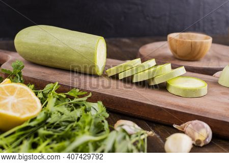 Slices Of Zucchini On A Wooden Cutting Board. Fresh Green Zucchini Whole And Sliced On A Chopping Bo