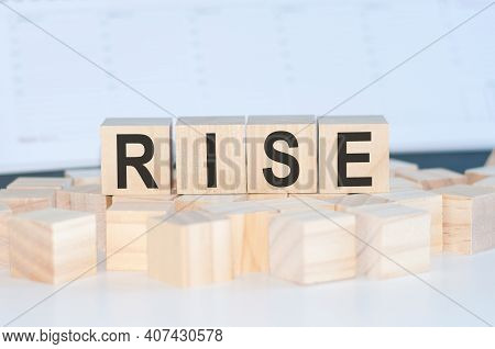Word Rise Cube Wood On Wooden Table White Background. Concept Rise Is Any Financial Compensation. Bu