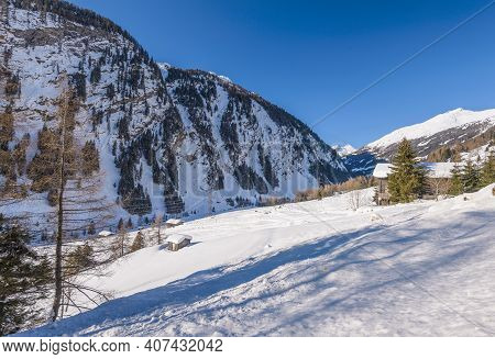 Winter Landscape With Valley In Snowy Mountains. Sunny Winter Day In Alps. Christmas Holiday And Win