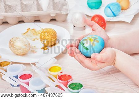 Child Paints Egg For Easter On A Wooden Table, Process Of Painting Eggs For Easter, Eggs Box, Easter