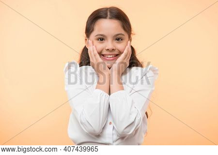 Full Of Excitement. Girl Happy Smiling Face Touches Her Cheeks Yellow Background. Schoolgirl Can Not