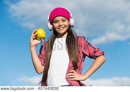 Go Organic. Happy Girl In Headphones Hold Apple Sunny Sky. Healthy Eating. Natural Food. Vegetarian
