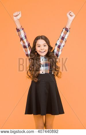 Celebrate The Childhood. Happy Girl With Raised Hands Yellow Background. Small Girl Back To School.