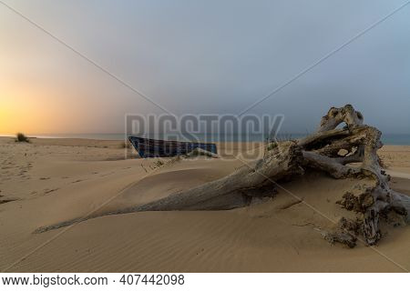 An Old Wooden Fishing Boat And Driftwood On A Beach After Sunset With Village Lights Behind