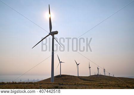 Windfarm Turbines In The Sun. Wind Turbines On An Arrid Field Of Grass In Washington State.