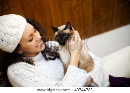 Young woman in winter in a cozy attic with her cat