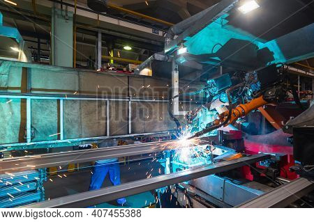 Welding Robot, Welds Metal Beams. Modern Welding Production. Bright Flashes, Sparks And Smoke.