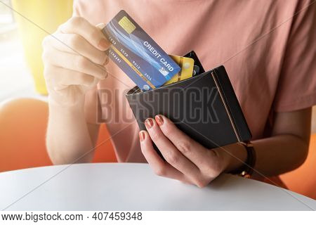 Cropped Shot View Of Female Hands Picking Credit Cards From Her Wallet. Credit Card Lets Cardholders