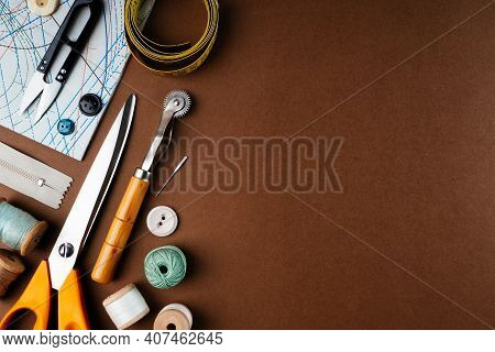 Flat Lay Composition Of Sewing Accessories, Scissors, Patterns On A Brown Background, Top View, Copy