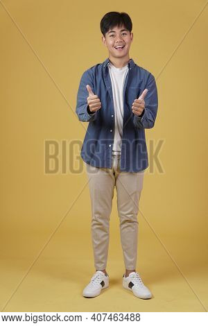 Portrait Of Smiling Positive Young Asian Man Dressed Casually With Thumb Up Gesture Approving Expres