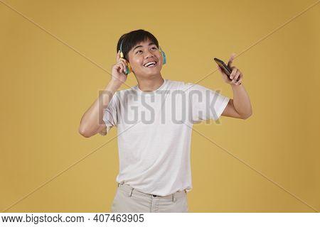 Portrait Of Happy Joyful Cheerful Young Asian Man Wearing Headphones Listening To Music On Smartphon