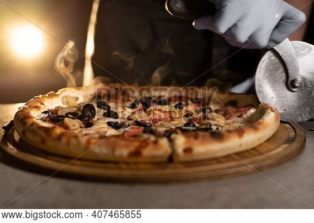 Chefs Hand With A Knife Cuts Hot Pizza With Olives And Salami On The Table On A Wooden Board In A Pi