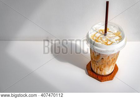 Iced Caramel Macchiato Coffee In Plastic Cup On A Wooden Table At The Cafe. Cold Espresso In The Cof