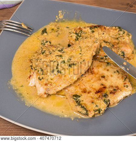 Fried Turkey Breast Steaks With Creamy Sauce On A Large Plate With Fork And Knife On A Wooden Table,