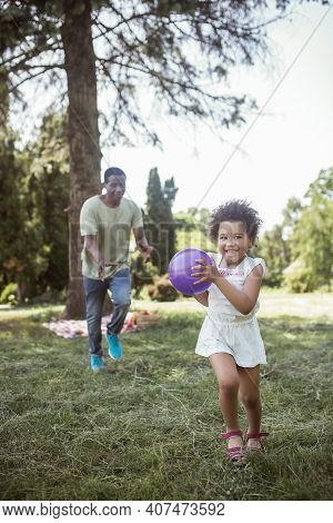 African American Man And His Cute Daughter Playing Ball In The Park