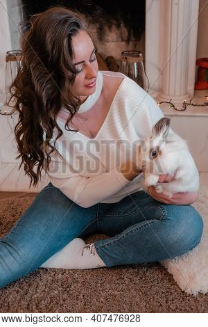 Atractive Young Woman Sitting Next To The Fireplace And Holding Rabbit. Pets And People. Home Sweet