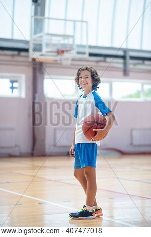 Dark-haired Boy In Sportswear Standing In Gym With A Bal In Hands