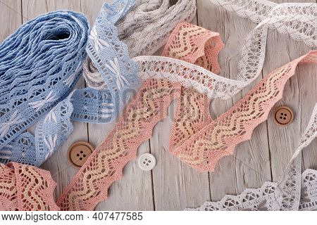 Pile Of Vintage Cotton Tapes And Round Buttons On Wood Background