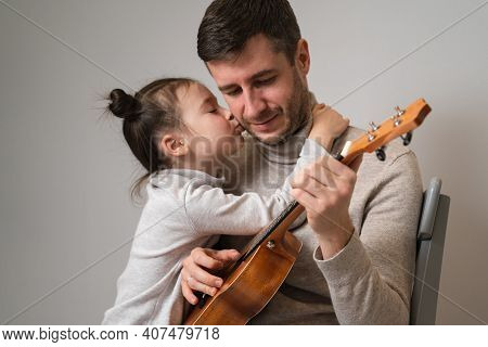 Dad Plays The Guitar With His Daughter. The Child Learns To Play A Musical Instrument With A Tutor.