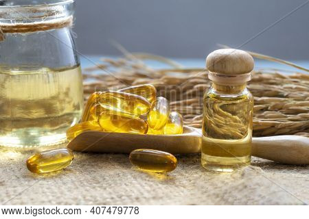 Bottles Of Rice Bran Oil With Rice Bran Oil Capsules With Dry Ear Of Rice As Background.