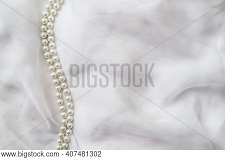 A Necklace Of Pearls Lies On A White Cloth