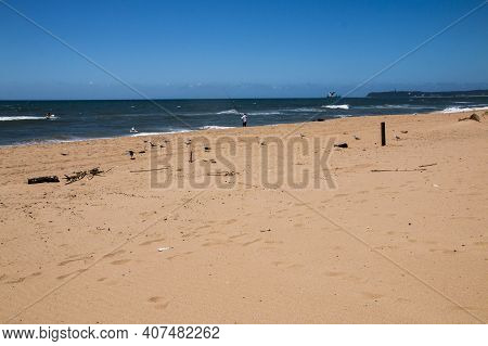 Stretch Of Beach With Waves Breaking In Deep Blue Sea
