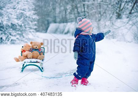 Full Growth Photo Of Toddler Girl In A Blue Overalls, Ultimate Gray Mittens, Scarf, Hat, Shoes Stand