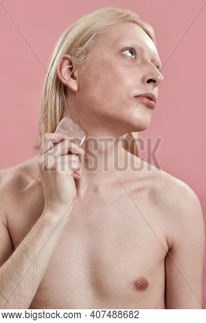 Young Caucasian Man With Long Blond Hair Massaging Neck Using Quartz Stone While Standing On Pink Ba