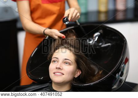Master Washes Her Hair In Sink For Client In Hairdressing Salon. Services Of Beauty Salons And Haird