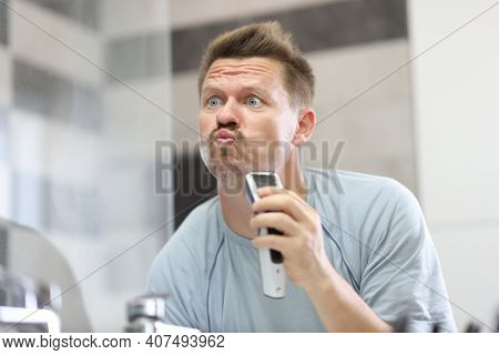 Man In Front Of A Mirror Shaves Off His Stubble With Machine. How To Properly Shave Off Facial Stubb