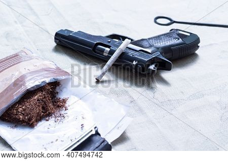Pistol And Tobacco. A Pistol Lying On The Table. Tobacco For Cigarettes. Front Angle View.