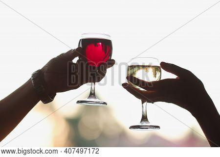 Men And Women Are Holding Glasses Of Red And White Wine. Romantic Date Concept