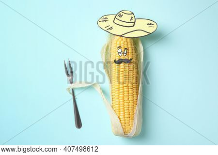 Mexican Man Made Of Corncob, Paper Hat And Fork On Light Blue Background, Top View