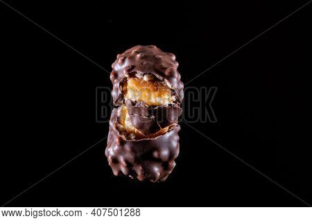Chocolate Candy With Caramel And Nuts. Broken Candy Into Pieces. Stretching Caramel. Chocolate Candy