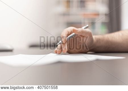 Close Up Of Man Hand Filling Out Form. Working In The Home Office