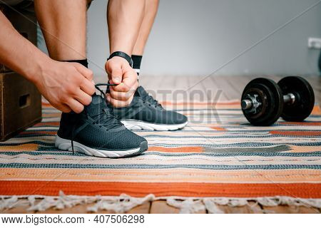 Young Man Tying  Black Shoelaces, Dumbbells And Bed In The Background
