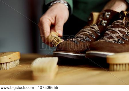 Man's Hand Clean Suede Shoes, Boots With A Brush On Wooden Background.
