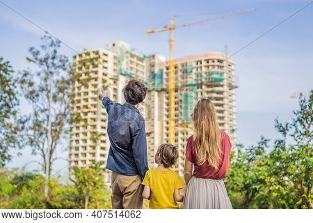 Family Mother, Father And Son Looking At Their New House Under Construction, Planning Future And Dre
