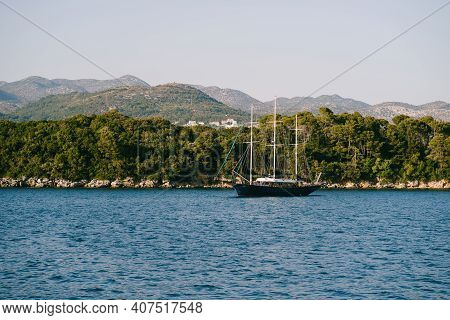 Beautiful Three-masted Wooden Ship Off The Coast Of Croatia. A Large Wooden Yacht Is Moored Along Th